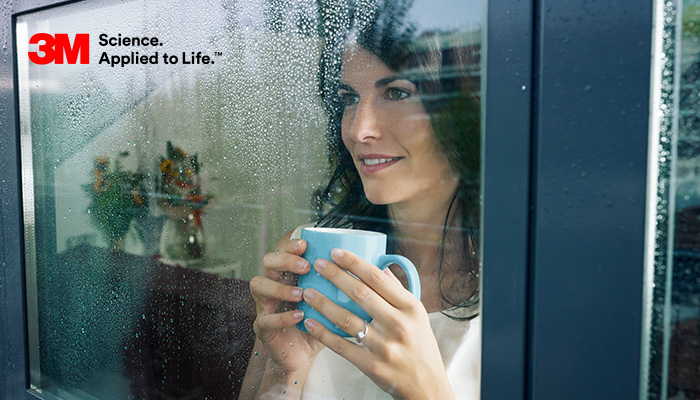 Lady holding a cup of coffee looking out of 3M Thinsulate window film